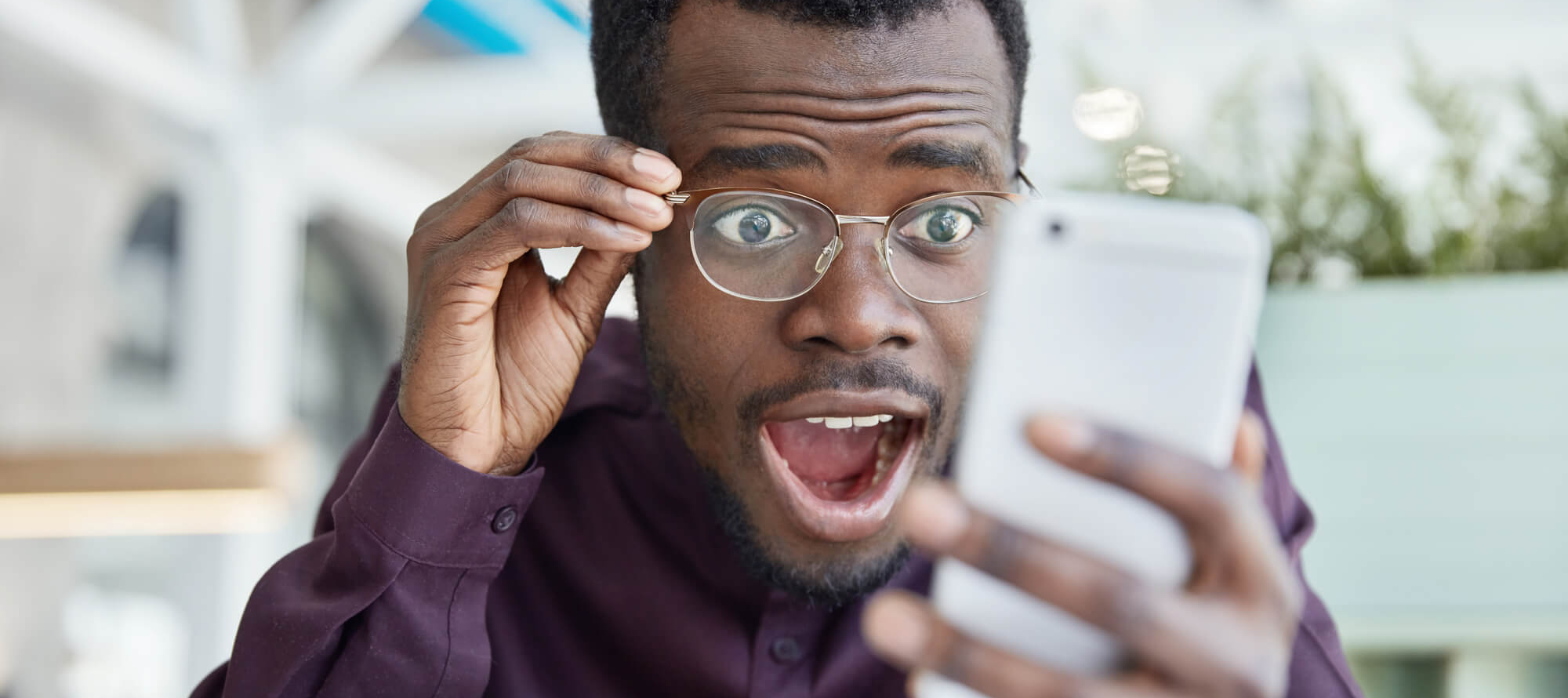 man holding glasses captivated by phone content
